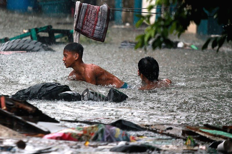 QUEZON CITY, July 17, 2018 - Residents wade through flood water brought by the heavy rain from tropical storm Son-Tinh in Quezon City, the Philippines, July 17, 2018.