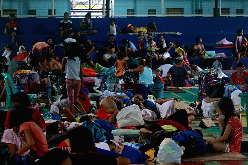 QUEZON CITY, July 18, 2018 - Residents take temporary shelter inside a covered basketball court as they evacuate from their homes due to the floods brought by tropical storm Son-Tinh in Quezon City, ...