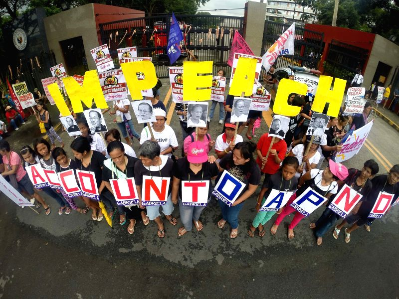 Activists display placards during a protest against President Benigno Aquino III outside the Philippine House of Representatives in Quezon City, the ...