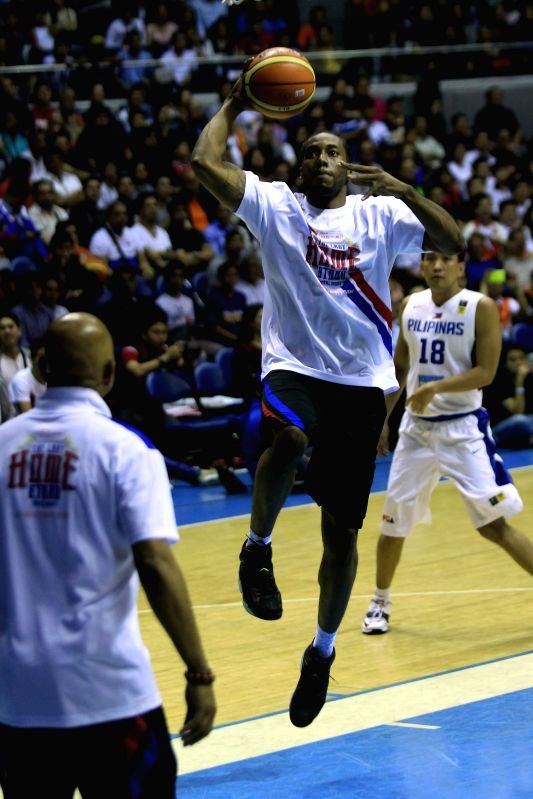 Kawhi Leonard (Top) of San Antonio Spurs goes to the basket during a charity event in Quezon City, the Philippines, July 22, 2014. Nine NBA players participated