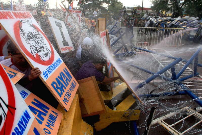Police disperse activists with water cannons during a protest rally in Quezon City, the Philippines, July 28, 2014. Protesters held a rally to show their dismay