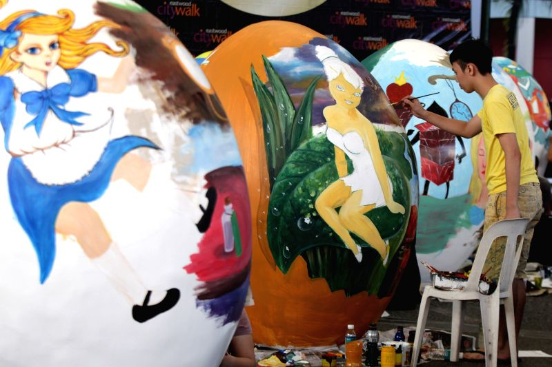 An artist paints a giant paper mache egg during the Giant Easter Egg Painting Competition in Quezon City, the Philippines, March 26, 2015. Various fairy tale ...