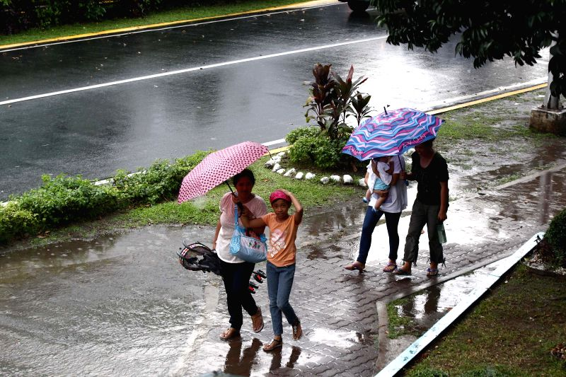 Quezon City: People walk with umbrellas in the rain in Quezon City, the Philippines, on Dec. 4, 2014. Typhoon Hagupit is packing maximum winds of 205 kph near the center and gustiness of up to 240 ...
