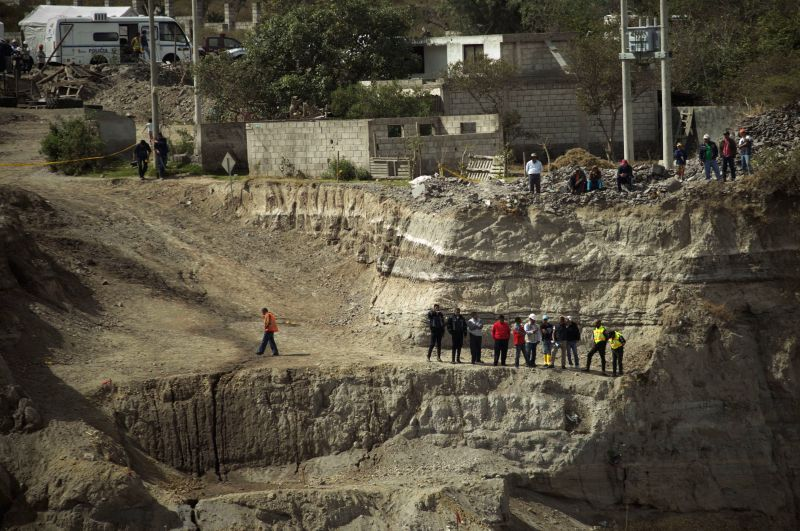 People look at the site of a landslide in Quito, capital of Ecuador, on Aug. 13, 2014. The death toll from a shallow 5.1- magnitude earthquake in Ecuador's capital ...