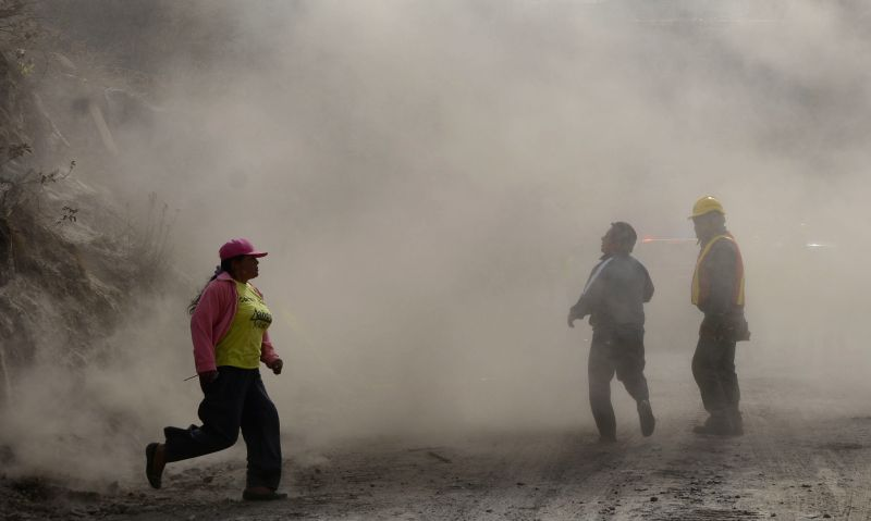 People walk amid dust at the site of a landslide caused by an earthquake in Quito, capital of Ecuador, on Aug. 12, 2014. A 5.1 magnitude earthquake rocked outside .
