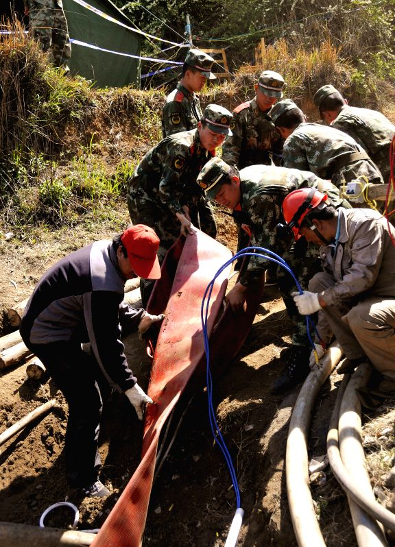 Rescuers lay water pipelines outside the flooded Xiahaizi coal mine where 22 miners were trapped underground in Qujing City, southwest China's Yunnan Province, ...
