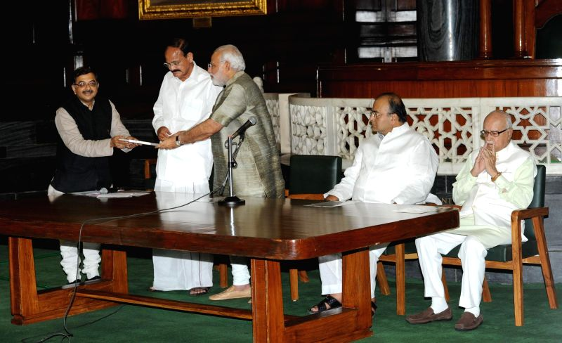 Rajya Sabha member Tarun Vijay presents Prime Minister Narendra Modi a book on him in Chinese language in Central Hall of Parliament on 22 July 2014. Also seen BJP veteran L.K. Advani, Union Minister - Narendra Modi, M. Venkaiah Naidu, K. Advani and Arun Jaitley