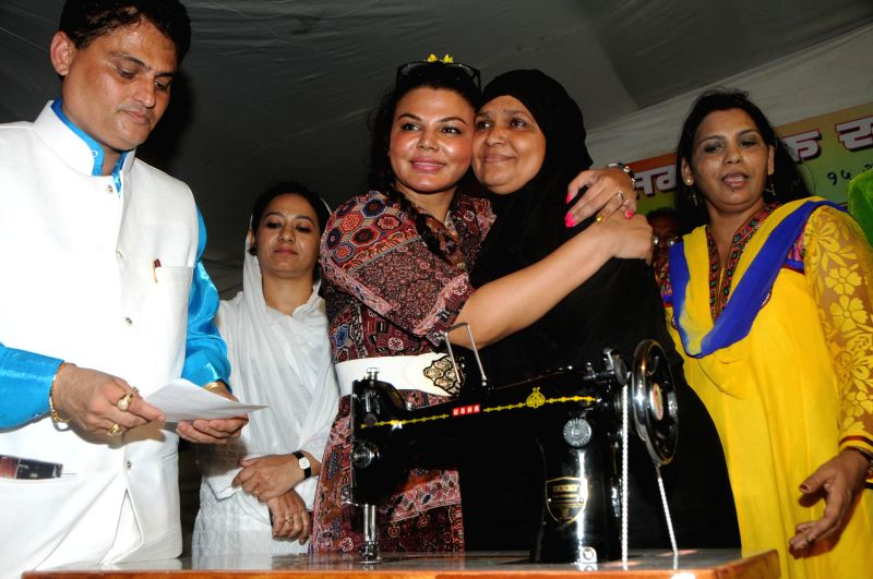 Rakhi Sawant along with Cyril D`Souza and Zeenat Qureshi distributing sewing machines to supports the cause of women empowerment an initiative by `Awaz Samajik Sanstha`of Cyril D`Souza in Mumbai, on .
