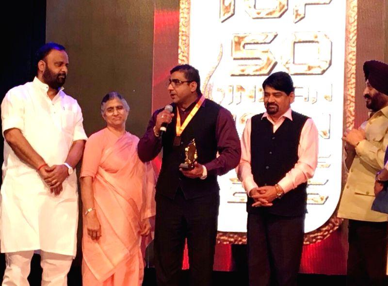 Ram Puri, Secretary of Jagadguru Kripalu Parishat, receiving the Top 50 Indian Icon award on behalf of the trust\'s president Vishakha Tripathi in Mumbai on Friday evening. UP Cabinet Minister ... - Vishakha Tripathi