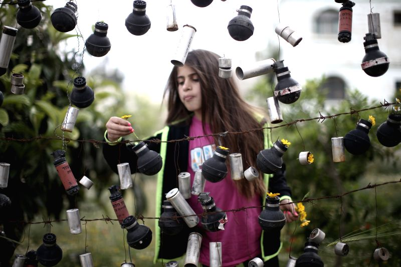 A Palestinian girl places flowers inside used tear-gas canisters fired by Israeli troops during past clashes in Nabi Saleh Village near the West Bank city of ...