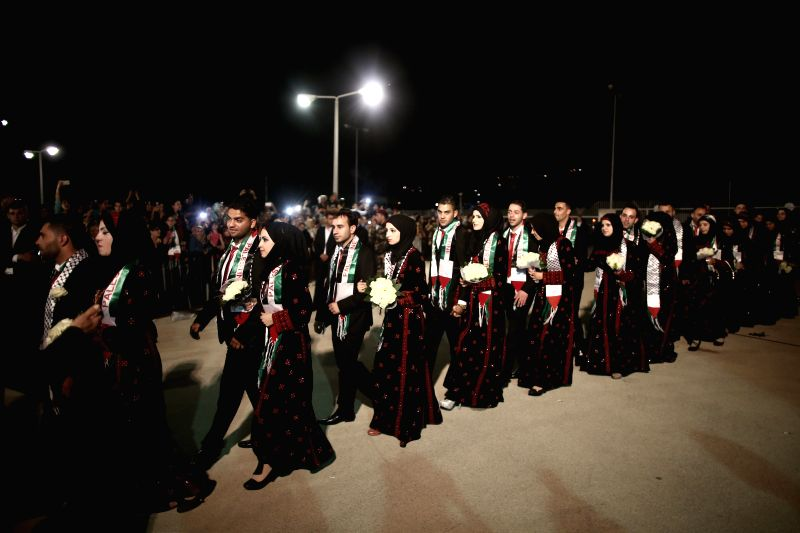 Palestinian couples take part in a mass wedding organized by the Palestinian presidency in the West Bank city of Jericho, on April 20, 2015. A total of 231 ...