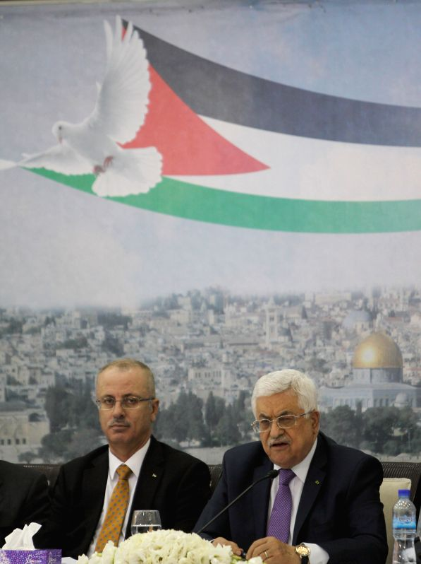 Palestinian President Mahmoud Abbas (R) speaks during a foundation meeting of a Jerusalem Fund with Palestinian businessmen at his office in the West Bank city of