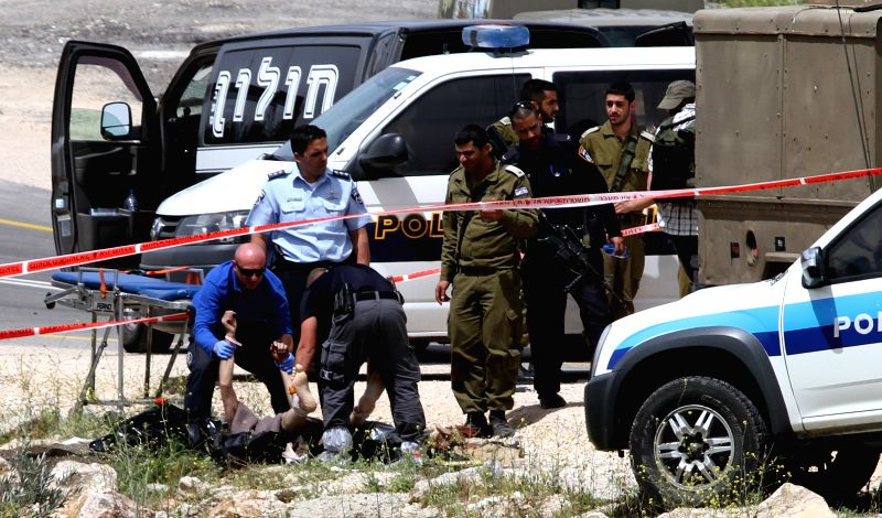 Israeli soldiers remove the body of Palestinian Mohammed Krakra, who was killed by Israeli soldiers after stabbing two Israeli soldiers, near Sinjel Village close ...