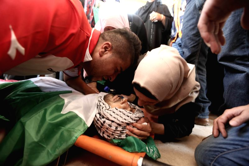 Relative of Palestinian Odai Jaber mourn over his body during his funeral near the West Bank city of Ramallah, Aug. 2, 2014. Odai Jaber, 19 years old, was killed ...