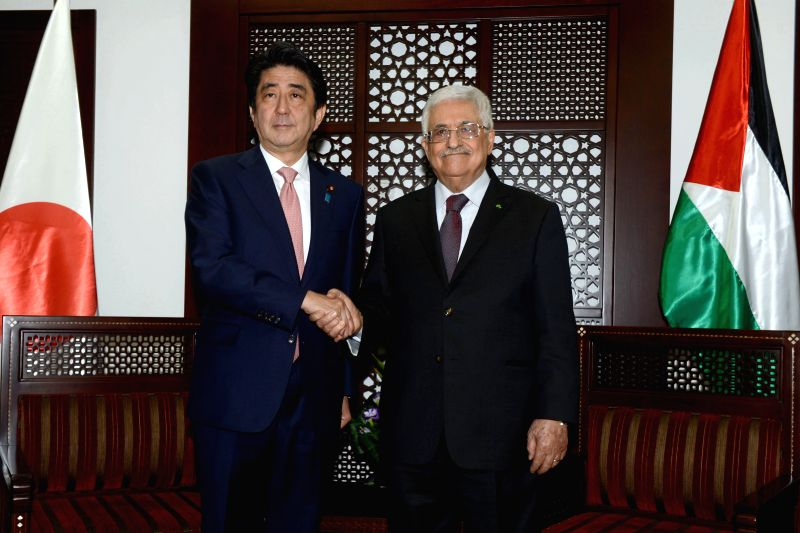 Japan's Prime Minister Shinzo Abe (L) shakes hands with Palestinian President Mahmoud Abbas during their meeting in the West Bank city of Ramallah on Jan. 20, ... - Shinzo Abe