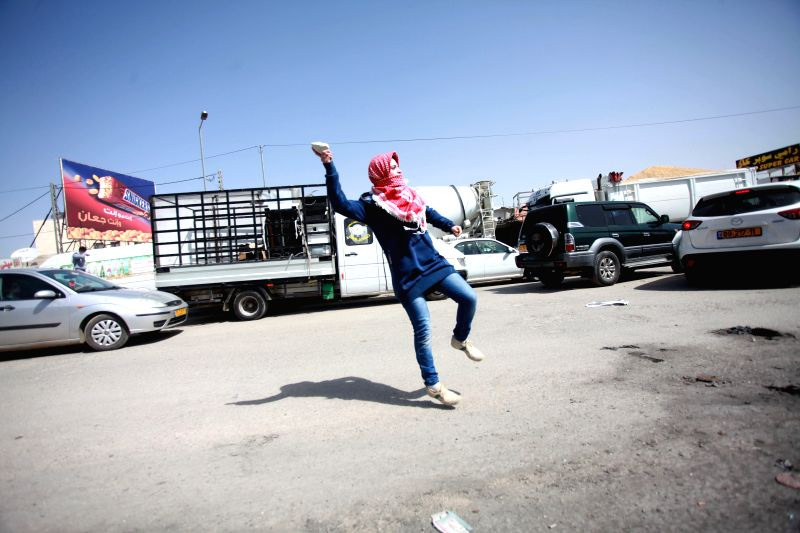 A Palestinian woman hurls stones towards Israeli soldiers during a protest at Qalandiya checkpoint in the West Bank city of Ramallah, March 7, 2015. (Xinhua/Fadi ...
