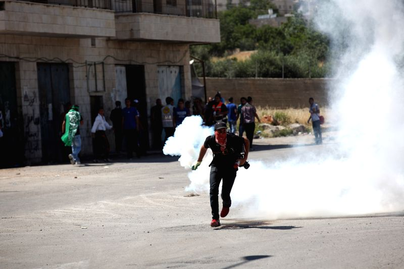 A Palestinian protester throws a tear gas back at Israeli soldiers during clashes outside Ofer Prison, on May 15, 2014. Israeli army killed two protesters and ...