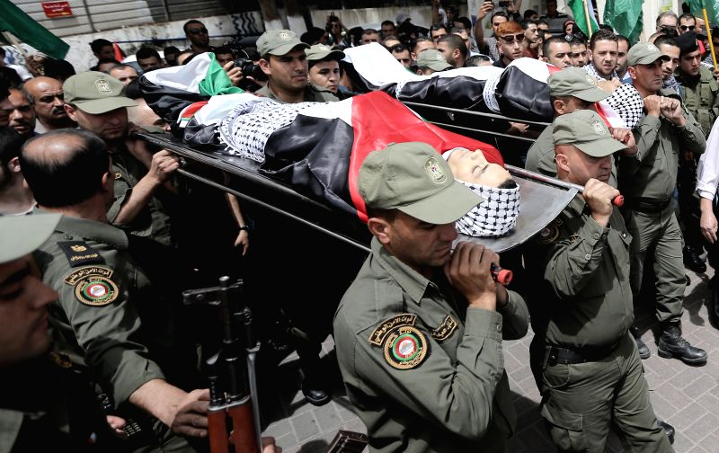 Palestinians carry the bodies of Nadeem Nowara and Mohammad Abu Daher during their funeral in the West Bank city of Ramallah, on May 16, 2014. Nowara and Abu Daher ..