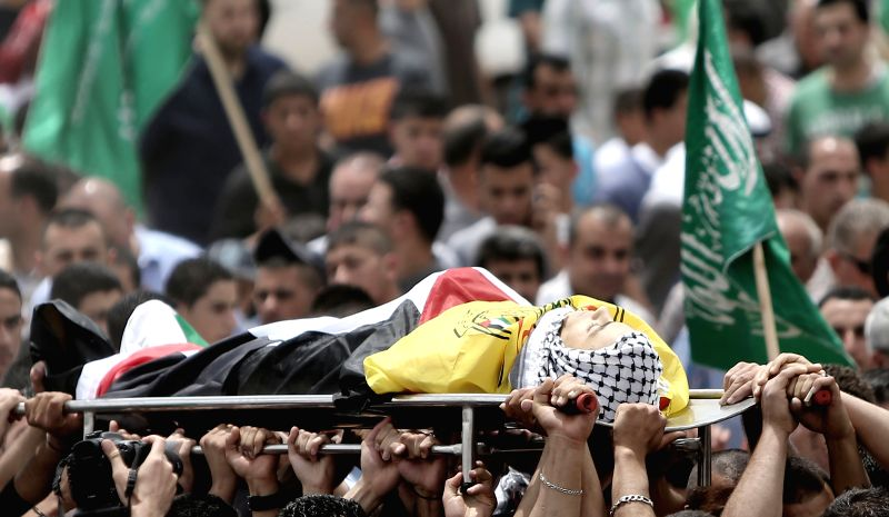 Palestinians carry the body of one of Nadeem Nowara and Mohammad Abu Daher during their funeral in the West Bank city of Ramallah, on May 16, 2014. Nowara and Abu ...