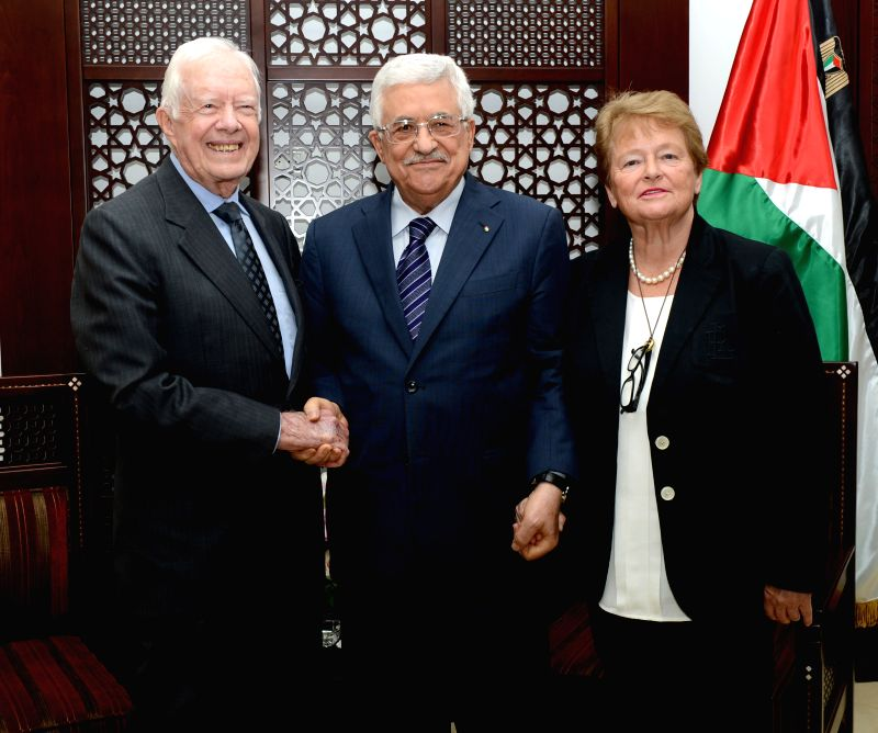 Palestinian President Mahmoud Abbas (C) shake hands with former U.S. president Jimmy Carter (L) before their meeting in the West Bank City of Ramallah on May. 2, ...
