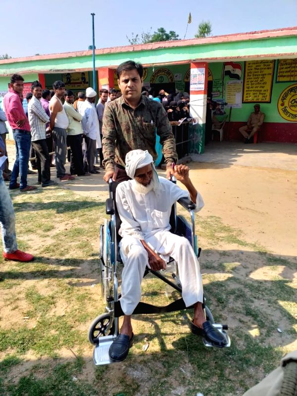 Rampur (UP): An old voter being escorted to a polling booth to cast his vote for the third phase of 2019 Lok Sabha elections, in Uttar Pradesh's Rampur, on April 23, 2019. (Photo: IANS/ECI)
