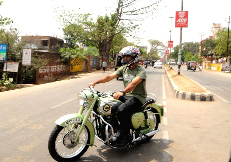 Indian cricket captain MS Dhoni rides a bike in Ranchi on April 6, 2015. - MS Dhoni