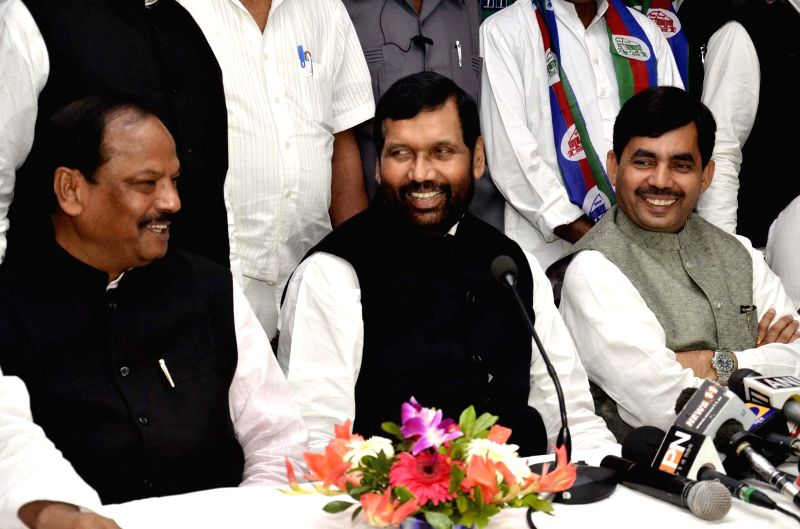 LJP chief and Union Minister for Consumer Affairs, Food and Public Distribution Ramvilas Paswan with BJP spokesperson Shahnawaz Hussain (R) and BJP leader  Raghuvar Das during a press ...