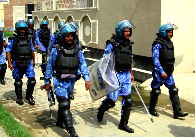 Rapid Action Force personnel flag march on the second day of communal violence between two groups over stone pelting incident at Atali village in Ballabgarh on July 3, 2015.