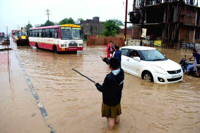 Rashtriya Swayamsevak Sangh (RSS) workers helps in clearing the traffic caused due to heavy rains, in Mathura, on July 27, 2018.