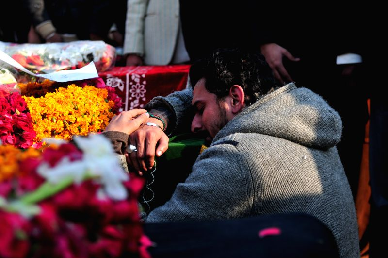 A man mourns over the death of his relative during the funeral ceremony of suicide blast victims in Rawalpindi, Pakistan, on Jan. 10, 2015. At least eight people