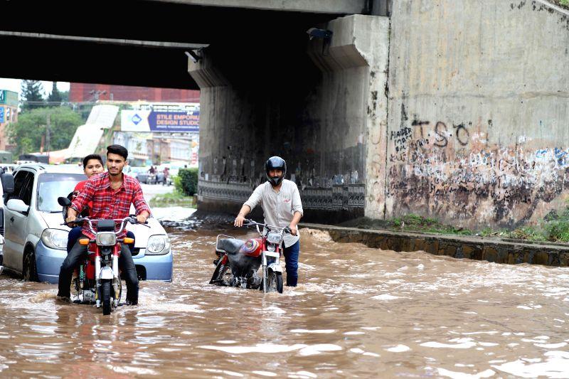 RAWALPINDI, July 25, 2019 (Xinhua) -- People push their bikes in flood water after heavy monsoon rain in Rawalpindi, Pakistan, July 25, 2019. (Xinhua/Ahmad Kamal/IANS)