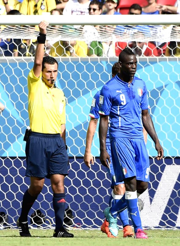 Italy's Mario Balotelli (R) gets a yellow card during a Group D match between Italy and Costa Rica of 2014 FIFA World Cup at the Arena Pernambuco Stadium in Recife, ...