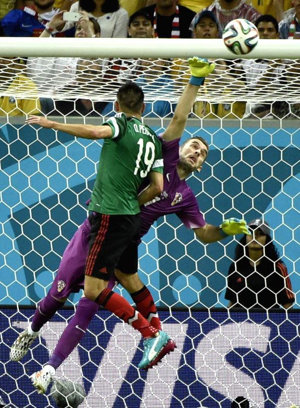 Croatia's goalkeeper Stipe Pletikosa (R) blocks a shot during a Group A match between Croatia and Mexico of 2014 FIFA World Cup at the Arena Pernambuco Stadium in ...