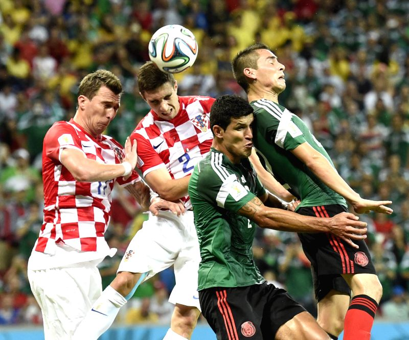 Croatia's Sime Vrsaljko (2nd L) competes for a header during a Group A match between Croatia and Mexico of 2014 FIFA World Cup at the Arena Pernambuco Stadium in ...