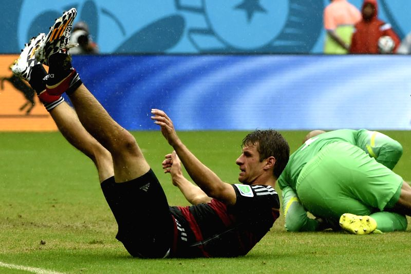 Germany's Thomas Muller (L) falls down during a Group G match between the U.S. and Germany of 2014 FIFA World Cup at the Arena Pernambuco Stadium in Recife, Brazil, .