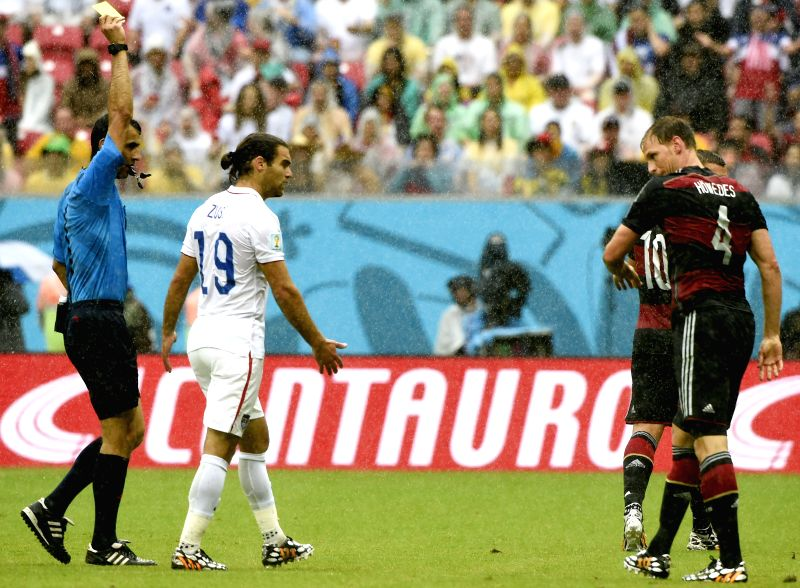 Uzbiekistan's referee Ravshan Irmatov (1st L) gives a yellow card to Germany's Benedikt Howedes (1st R) during a Group G match between the U.S. and Germany of 2014 ..