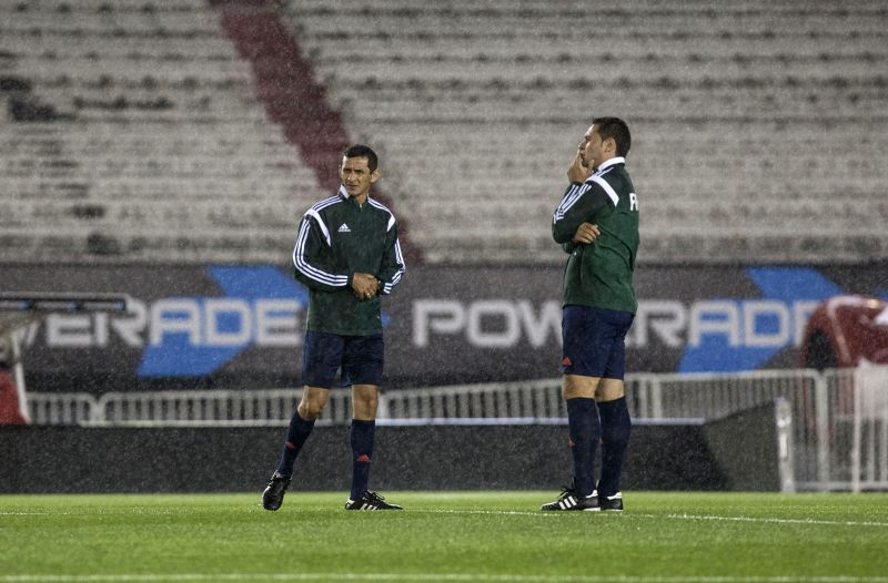 Referee Antonio Arias (L) checks the field before the announcement of suspension due to the rain of the qualifying match for the Russia World Cup 2018 between ...