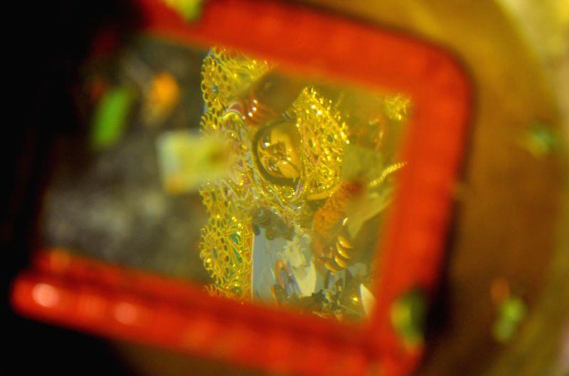 Reflection of goddess Durga in a mirror kept in a vessel containing water on Vijaya Dashmi in Kolkata, on Sept 30, 2017.
