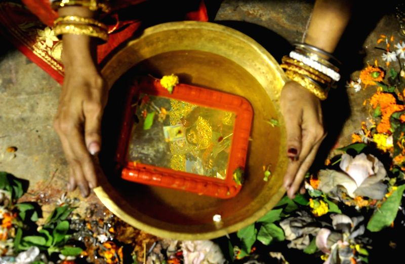 Reflection of goddess Durga in a mirror kept in a vessel containing water on Vijaya Dashmi in Kolkata, on Sept 30, 2017.