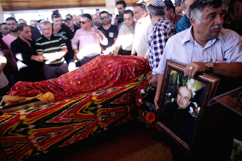 Relatives and friends mourn during the funeral of Israeli Reuven Aviram, who was killed in a stabbing spree at a chapel on Tel Aviv's seafront on Thursday, in ...