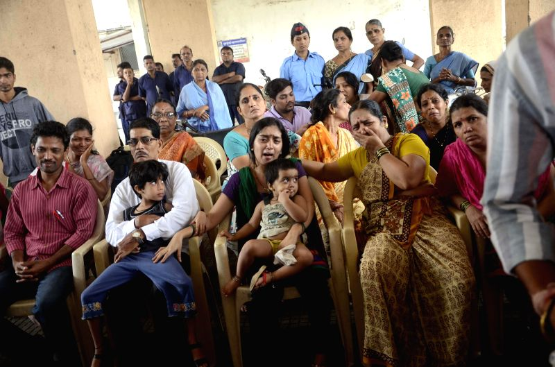 Relatives of fireman Nitin Yevlekar, who was killed dousing flames at the 22-storeyed Lotus Park building where a fire broke out yesterday (18th July 2014) at his funeral at Fire Brigade Head ...