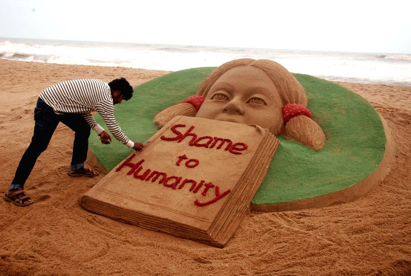 Renowned sand artist Sudarsan Pattnaik condemns rape of a 6-year-old in Bangalore through his art on Puri beach in Odisha on July 22, 2014.