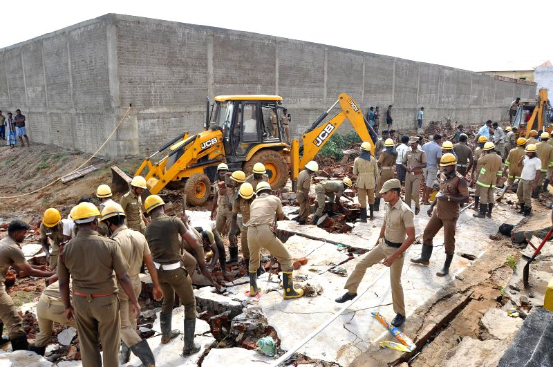 Rescue operations underway at the site where a wall which was being built for a private warehouse collapsed on the huts abutting it in Tamil Nadu's Tiruvallur district on July 6, 2014. Eleven ...