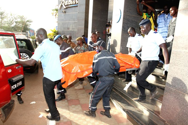 Rescue team members carry out a body of a victim from the Radisson Blu hotel in Bamako, Mali, Nov. 20, 2015. Three Chinese citizens were killed in a hostage-taking ...