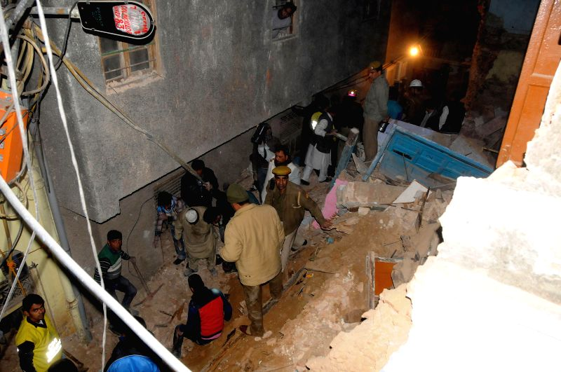 Rescuers look through debris at the spot where a two-story building collapsed at Sita Ram Bazar, near Turkman Gate in old Delhi on Dec. 21, 2014.
