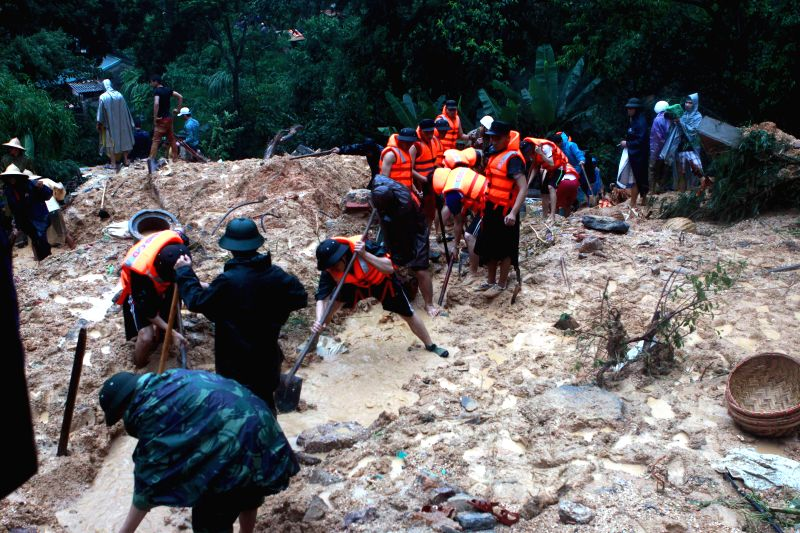 Rescuers work at a collapsed house in Ha Long city, Quang Ninh province, northeastern Vietnam, July 28, 2015. Floods and landslides triggered by heavy downpour in ...