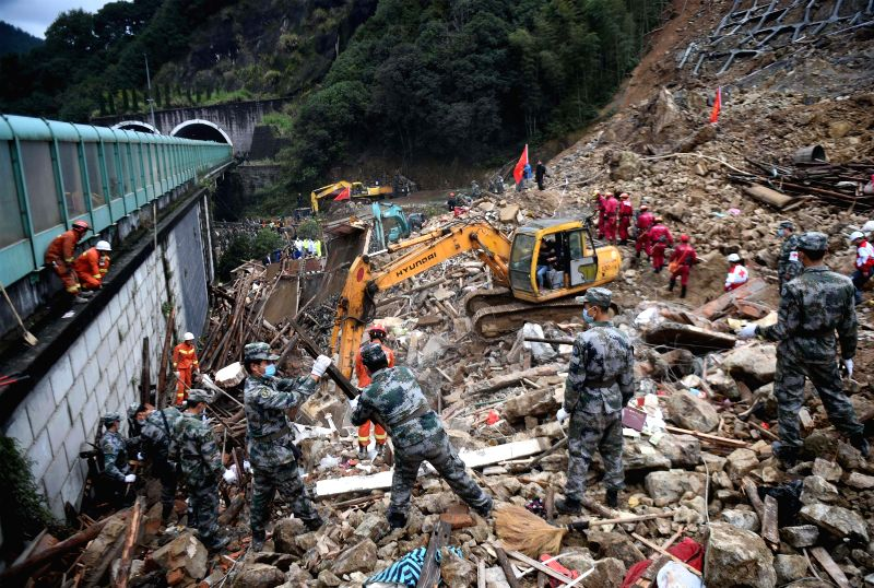 Rescuers work at the site of a landslide in Lidong Village of Yaxi Township in Lishui, east China's Zhejiang Province, Nov. 14, 2015. Nine people were confirmed dead ...