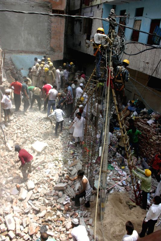 Residents look for survivors as a three storey residential building collapsed at Inderlok in Delhi on June 28, 2014.