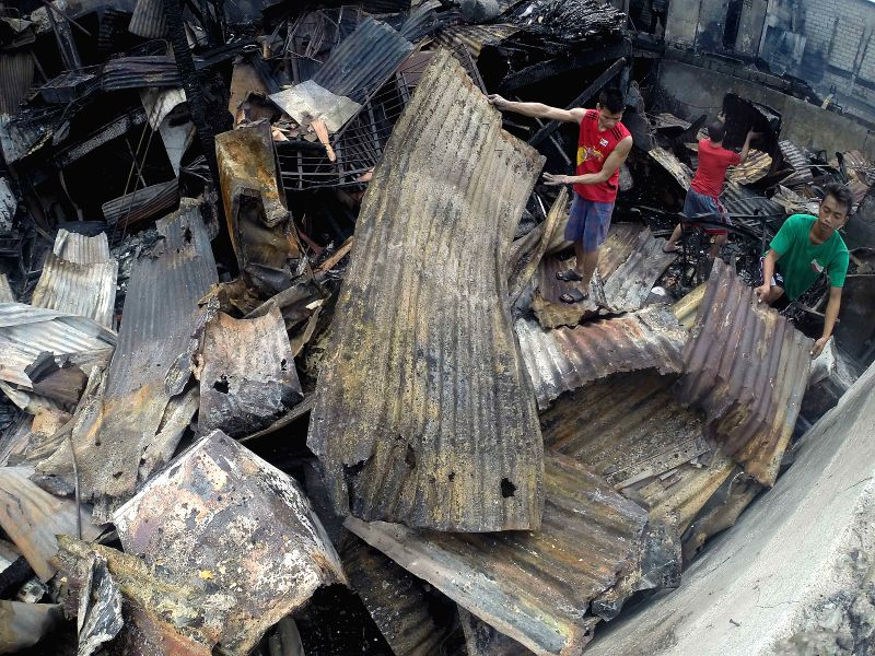 Residents look for their belongings from their burnt houses after a fire at a slum area in Manila, the Philippines, Dec. 5, 2015. More than 500 shanties were razed in ...