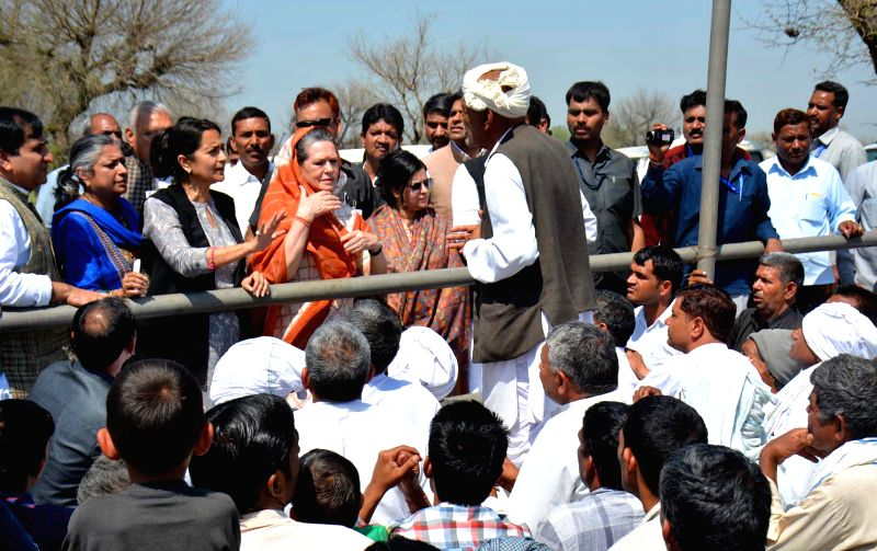 Congress president Sonia Gandhi interacts with farmers during her visit to Rewari of Haryana on March 21, 2015.